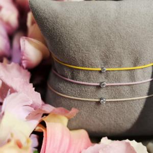 string bracelets displayed on jewellery cushion